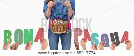 Hands holding up bona pasqua against portrait of a girl holding a basket full of easter eggs