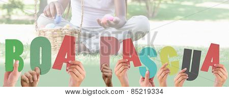 Hands holding up boa pasqua against little girl sitting on grass counting easter eggs smiling at camera