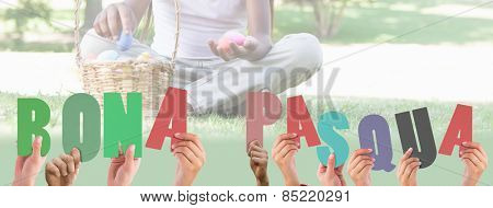 Hands holding up bona pasqua against little girl sitting on grass counting easter eggs smiling at camera