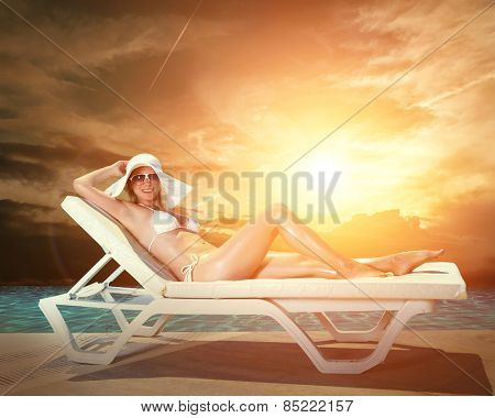 Beautiful female in white bikini near the waterpool under sun light