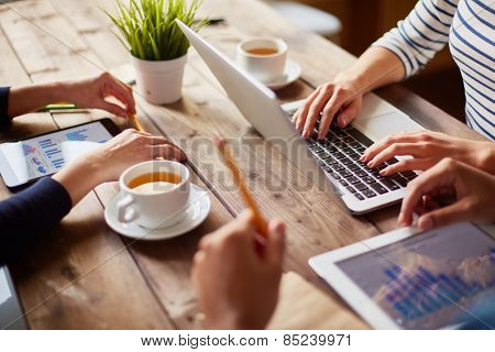 People using different devices at one table