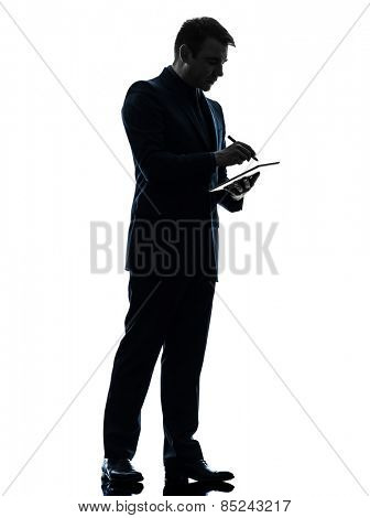 one  business man holding digital pen stylus tablet in silhouette on white background