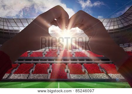 Woman making heart shape with hands against football stadium full of england fans