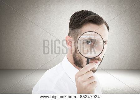 Geeky businessman looking through magnifying glass against grey room
