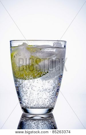 a glass of fresh drinking water and a lime. bottled water as a thirst quencher.