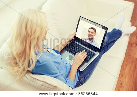 home, technology, communication and people concept - smiling woman sitting on couch and chatting with laptop computer at home