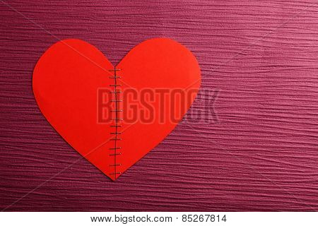 Broken heart stitched with staples on colour background