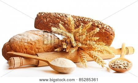 Fresh bread with wheat, flour and sunflower seeds in wooden spoons isolated on white