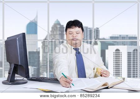 Businessperson With Burger Working On Table