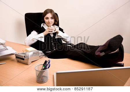 Young Businesswoman  Sitting In Chair And Holding A Cup Of Tea