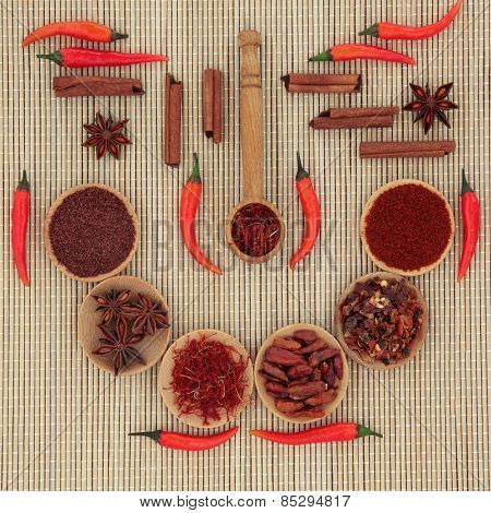 Red chilli pepper and spice selection in wooden bowls, spoons and loose over bamboo background.