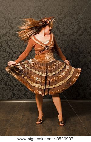 woman in brown dress dancing next to the wall.