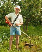 Smiling gardener is fixing lawn trimmer in garden poster