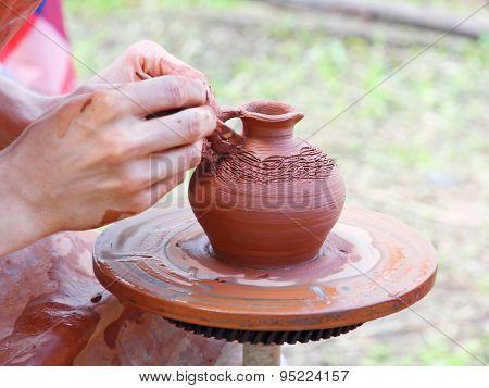 Potter makes on pottery wheel clay pot.Taken closeup. poster