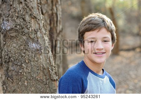Cute Boy Smiling Next To Tree