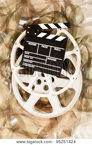 Cinema movie reel and clapper board with 35 mm unrolled filmstrip background vertical frame poster