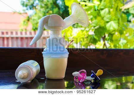 Breast pump, bottle of milk and pacifiers on the table