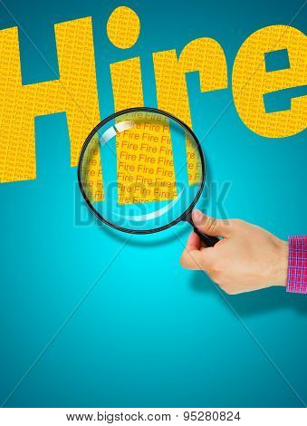 Human hand holding magnifying glass reading the word HIRE hiding the opposite message FIRE. Yellow word on a turquoise background. Antonym hidden reality concept Hidden message poster