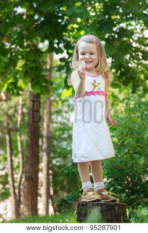 Full length portrait of smiling blonde girl with white Taraxacum officinale or dandelion seeds