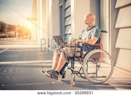 Man On Wheel Chair Using Computer