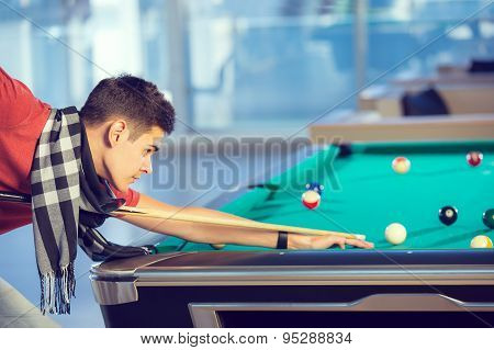 Young man playing billiards in billiard club