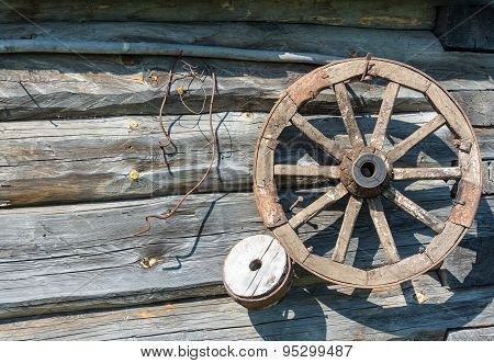 Wooden Wheel On The Log Wall.