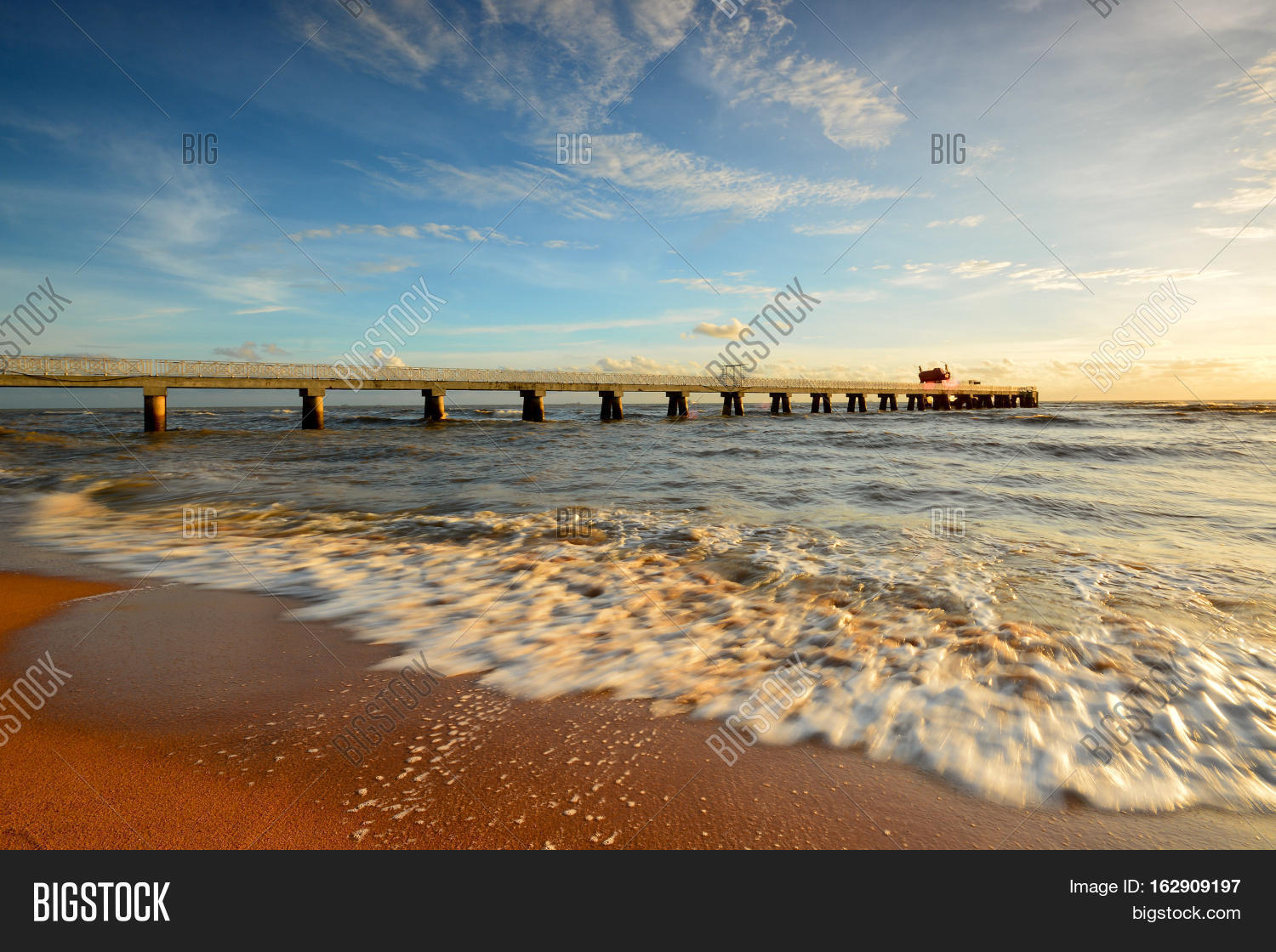 Beautiful Scenery Of Sunset Sky At Beach With Wave Motion Foreground And Long Jetty