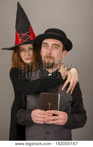 Beautiful witch with red hair and bearded priest on gray background