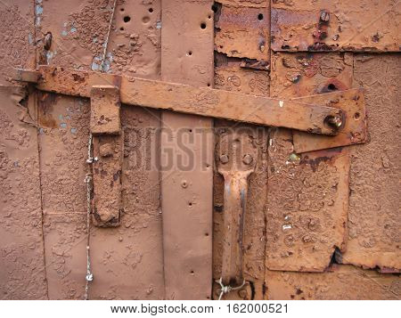 Rusty brown painted latches on a garage door,