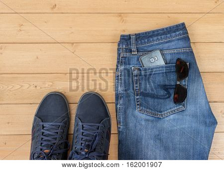 Men's Jeans And Accessories On The Wooden Floor.