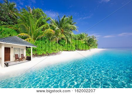 Overwater Bungalows On Tropical Island With Sandy Beach, Palm Trees And Turquoise Clear Water