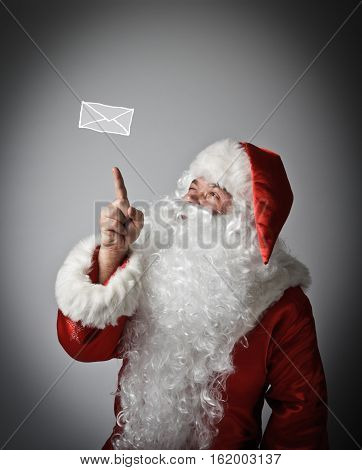 Santa Claus is looking at the letter. Santa Claus is pointing at the letter.