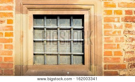 square window with iron grating and stone jamb in ancient castle