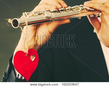 Valentines day love melody concept. Flute music playing man flutist musician performer. Male hands with instrument and red heart close up