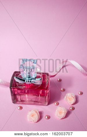 Pink aromatic perfume with polka dot ribbon and pink roses on pink background