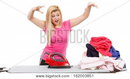 Housewife problems concept. Shocked angry woman standing behind ironing board having lot of clothes to iron. Studio shot on white background
