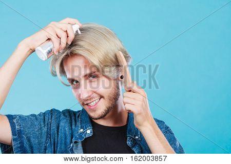Man Applying Spray Cosmetic To His Hair