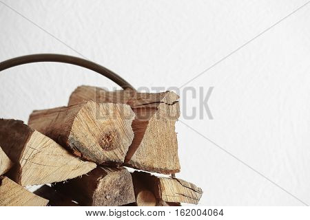 Stack of firewood on light blurred background, close up view