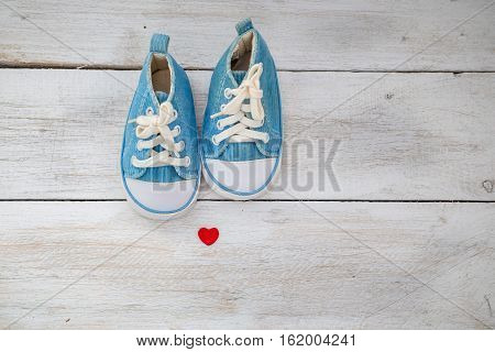 small baby blue sneakers on a white wooden background. baby shoes