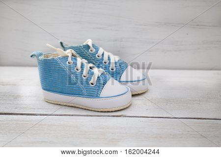 blue shoes for baby boy on a white wooden background