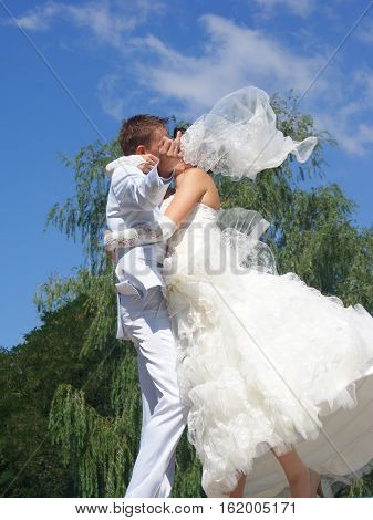 Beautiful bride kissing couple. Groom show finger with the ring.