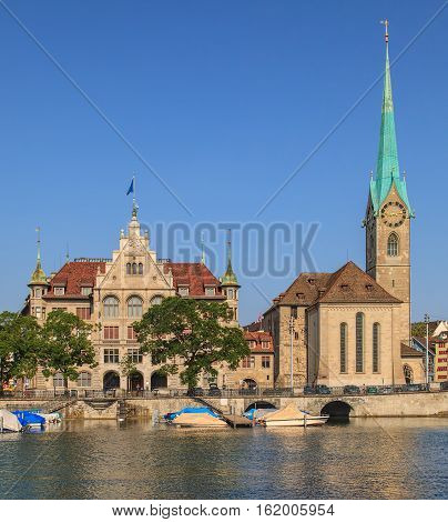 Zurich, Switzerland - 14 July, 2013: the City Hall building decorated with flag of Zurich and the Fraumunster Cathedral. Zurich City Hall houses the administration of the city, the Fraumunster Cathedral is a well-known landmark of it.