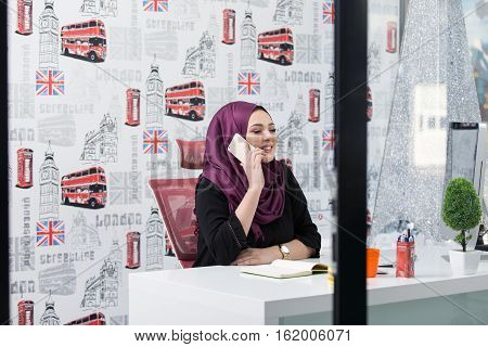 Attractive Muslim young woman working in office on computer.