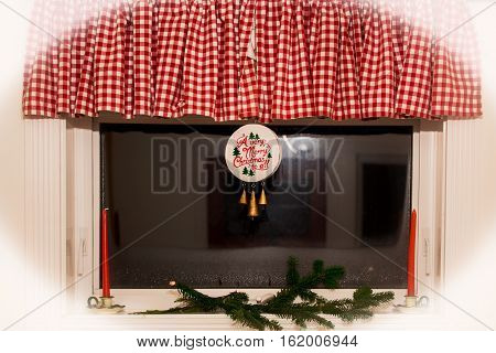 A window with festive ornament hanging from red checkered curtain decorated with Christmas candles ond green tree bough in white vignette