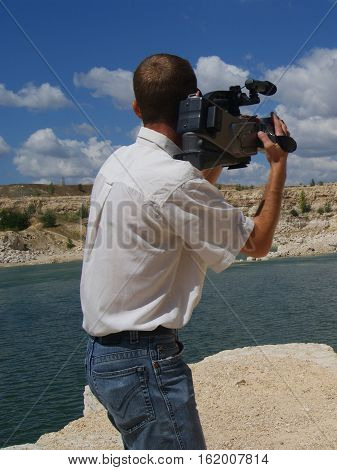 Cameraman outdoors. Man wearing white shirt and jeans.