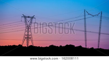 Electricity pylon making a silhouette against the setting sun
