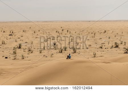 Man tourist in desert rub al khali in Oman sitting in sand view landscape