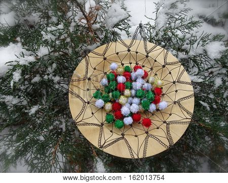 Red, green, white, and gold yarn pom pom decorations form the center of a crocheted wire basket on a bamboo plate with evergreen branches and snow in the background.
