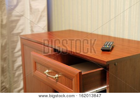 commode with an open drawer and a clicker on it in a hotel room