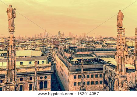 Old photo with view over Milan from the top of the gothic cathedral Milan Cathedral Italy. Church's roof statues in the foreground skyscrapers of the city in the background.Vintage processing.